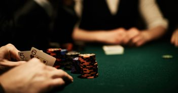 Human hands holding open cards and hiding them behind gambling chips