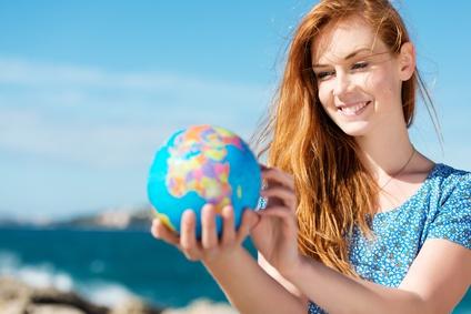 junge frau mit globus am meer © contrastwerkstatt